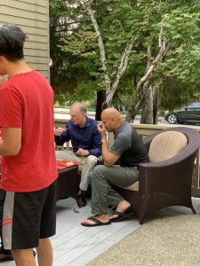 Haresh Sangani sits alongside other HItech Advisors employees outside our offices, enjoying a plate of BBQ.