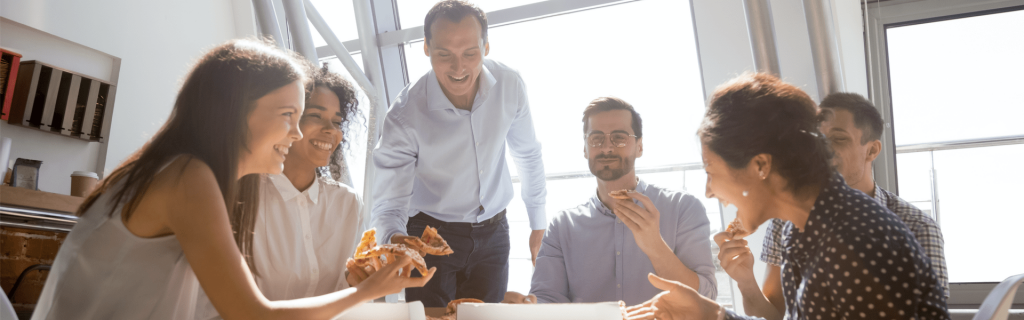 Stock photo of a business team eating pizza at a table.